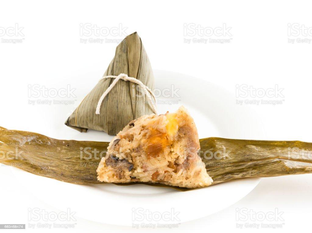 Chinese rice dumpling (Zongzi) stuffed with peanuts, mushroom, sweet mashed taro, marinated steamed pork, Ginkgo Biloba and salted egg yolk over bamboo leaf and white plate stock photo