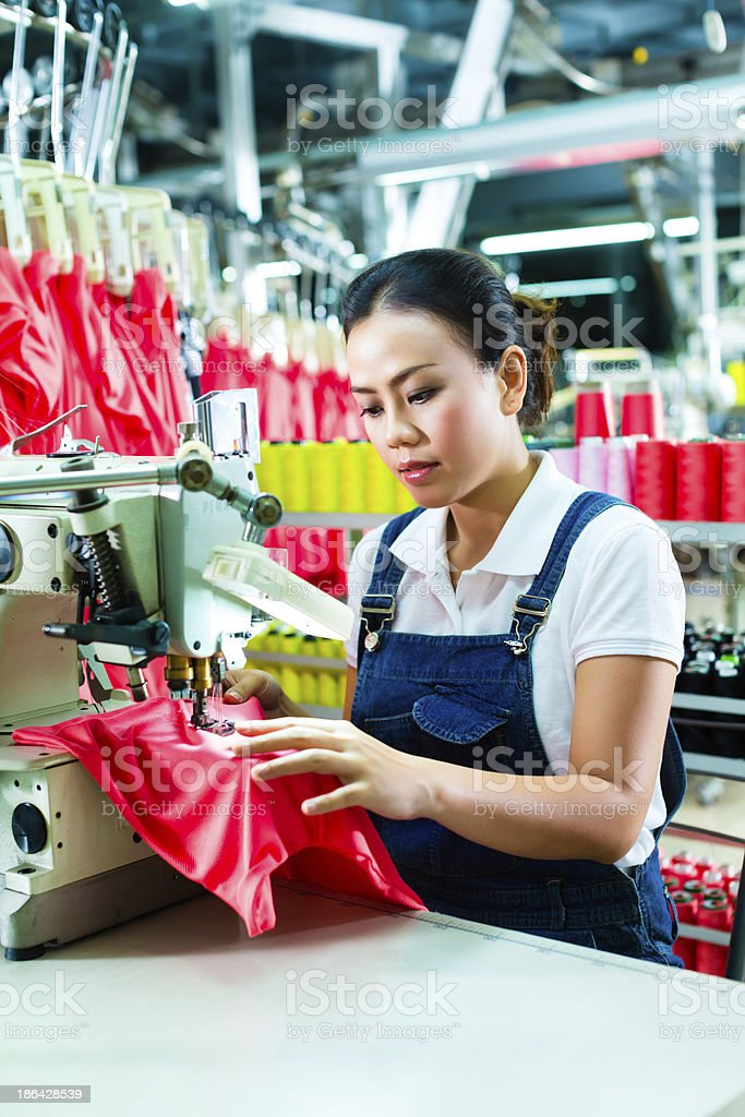 Chinese seamstress in a textile factory stock photo