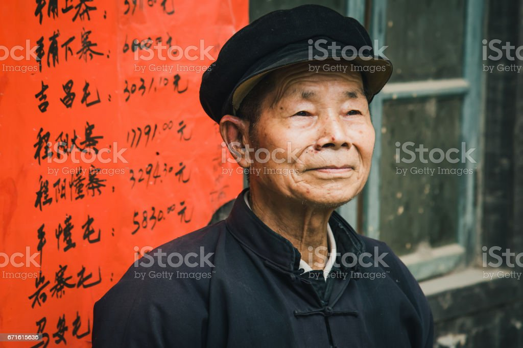Chinese senior man looking confident standing outside of small...