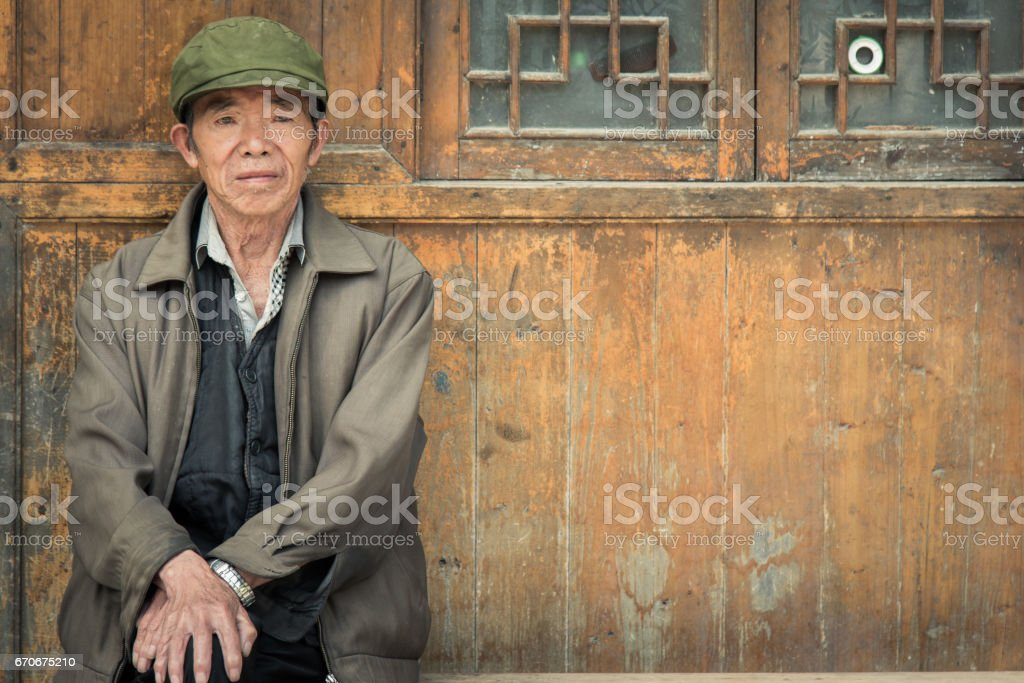 Chinese Senior Man sitting on bench in front of his home in Zhaoxing China stock photo