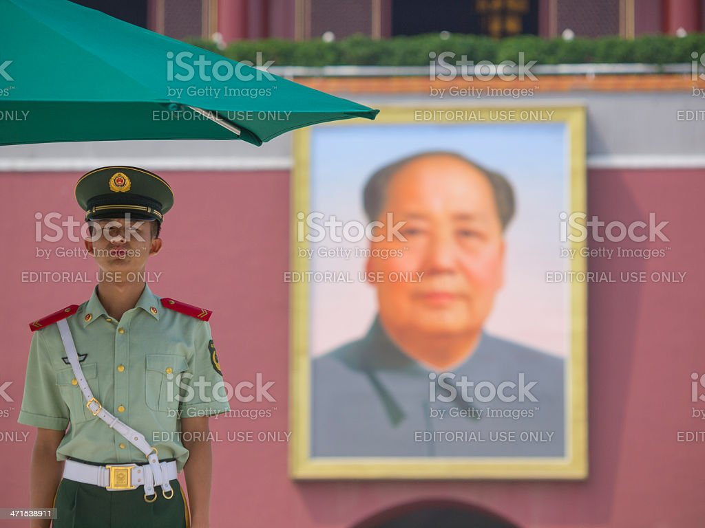 Chinese soldier by Mao Zedong portrait stock photo