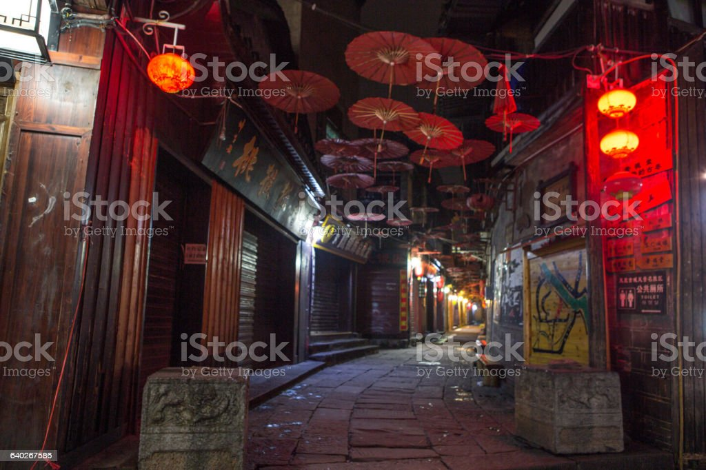 Chinese street with red umbrellas hanging, ancient village stock photo