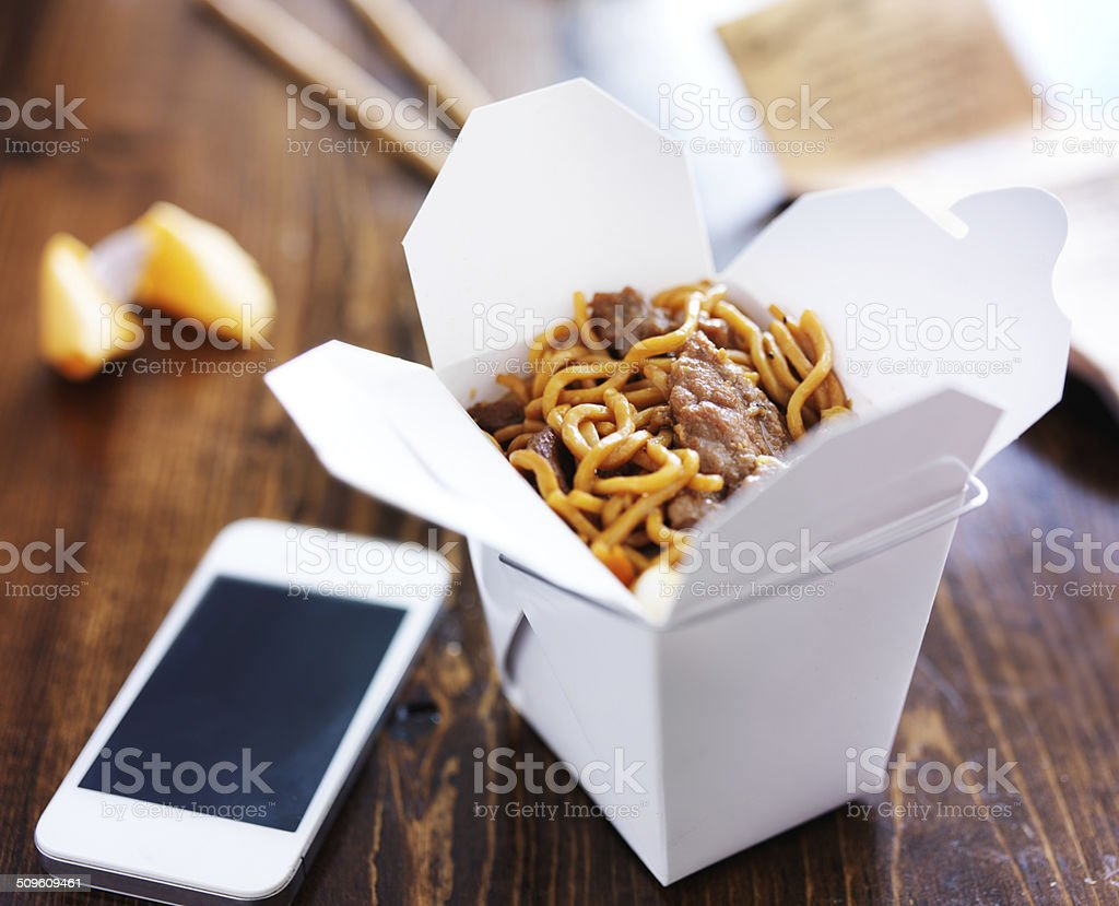 chinese take out with smart phone on table and menu stock photo