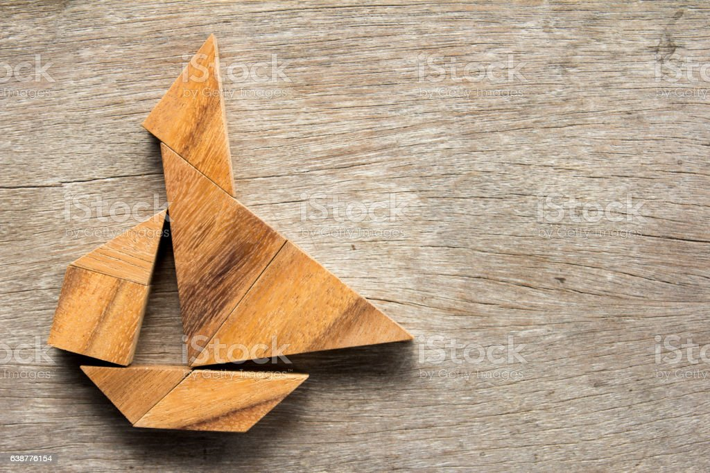 Chinese tangram puzzle in sail boat shape on wooden background stock photo
