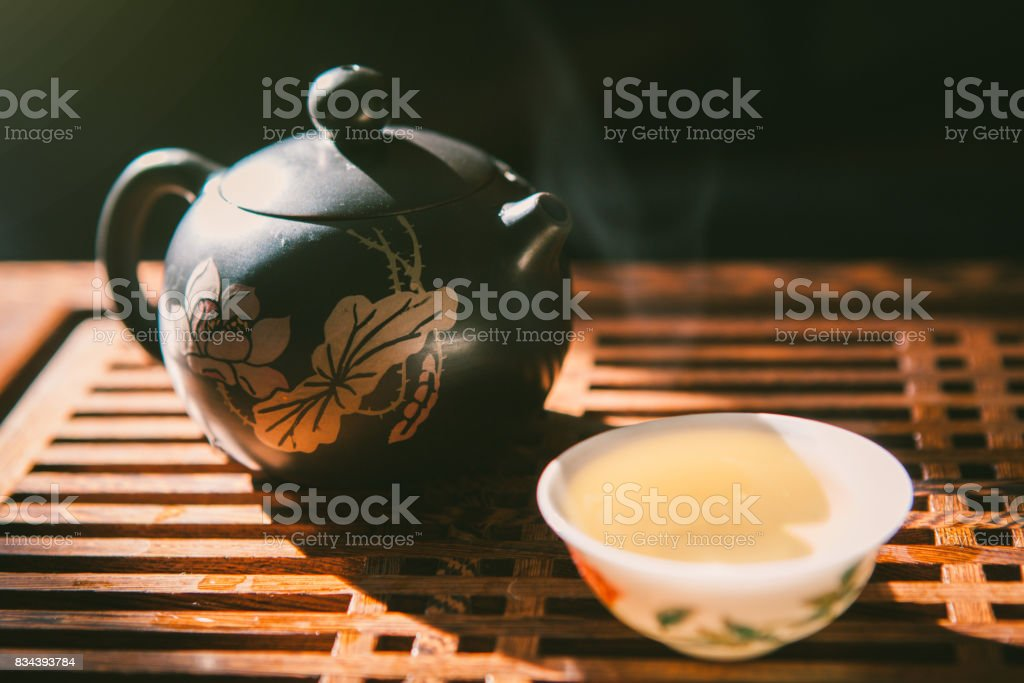 Chinese tea ceremony. Teapot and a cup of green puer tea on wooden table. Asian traditional culture. stock photo