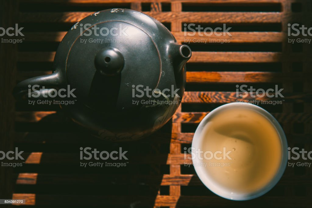 Chinese tea ceremony. Top view tea set: teapot and a cup of green puer tea on wooden table. Asian traditional culture. stock photo