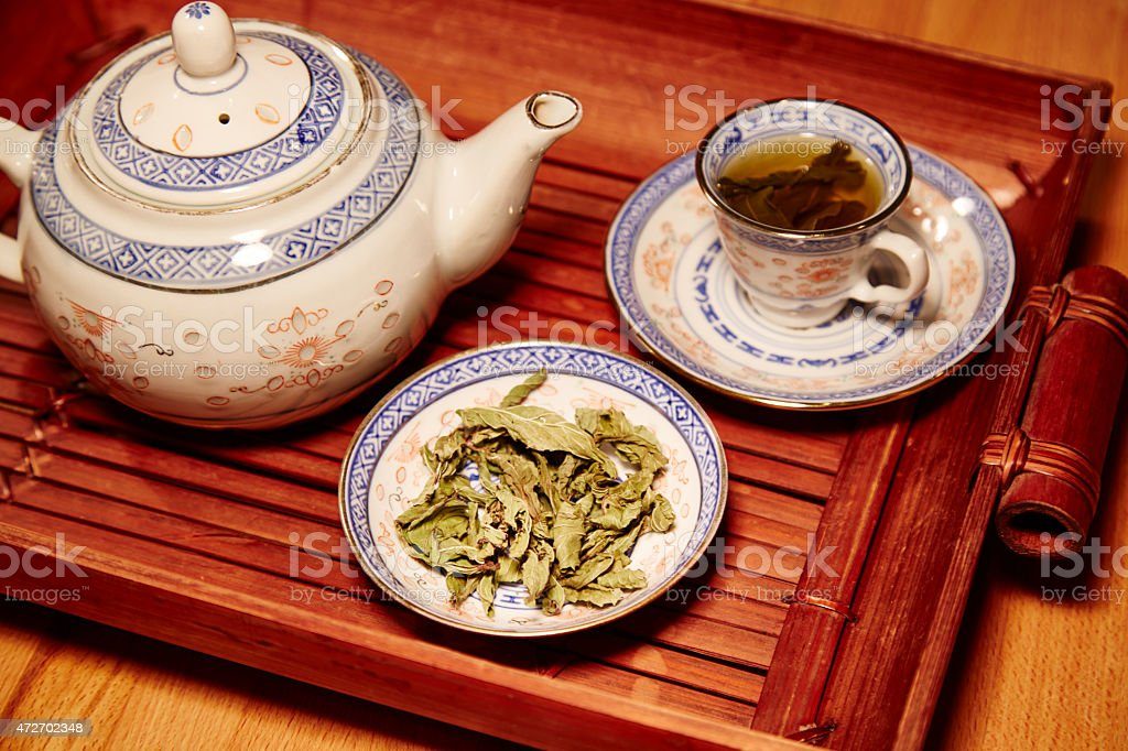 Chinese tea service, with leaves of green tea stock photo