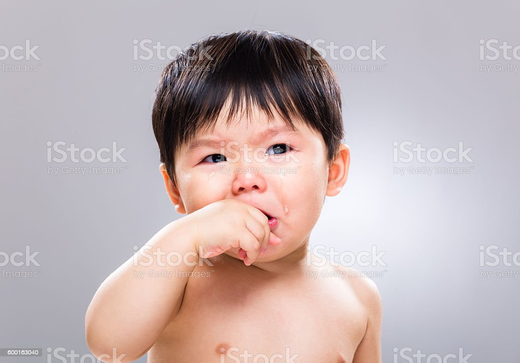 Chinese toddler sucking fingers stock photo