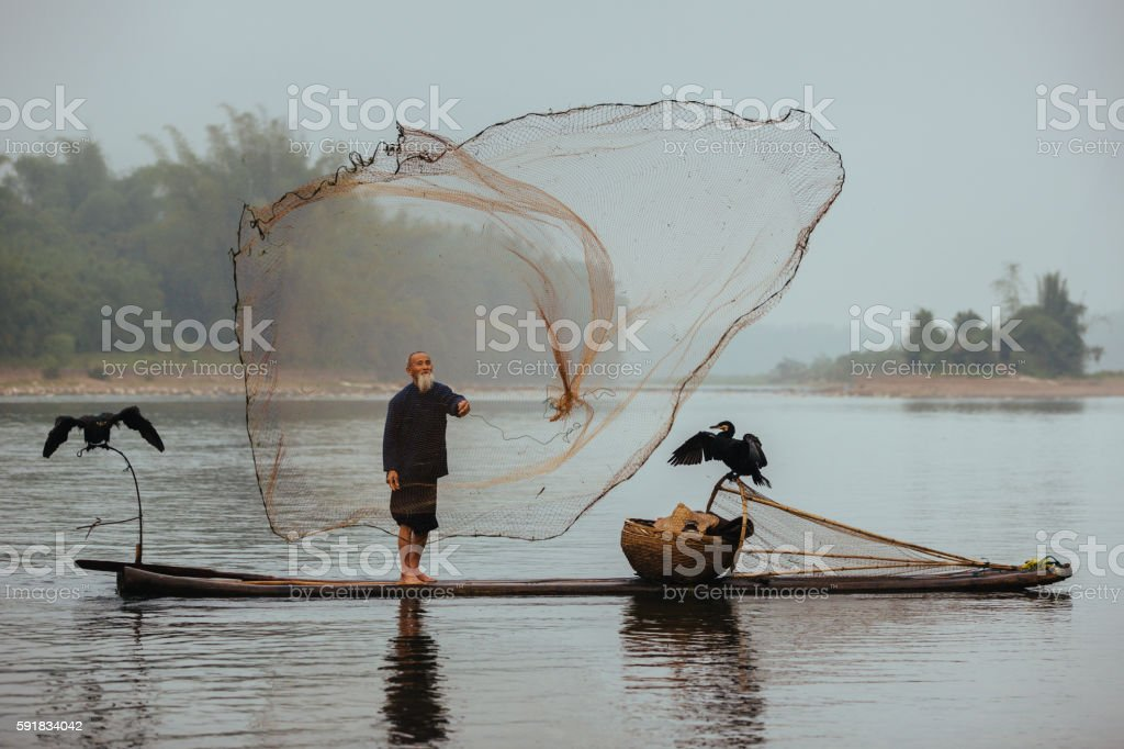 Chinese traditional senior fisherman throwing fishing net Li River China stock photo