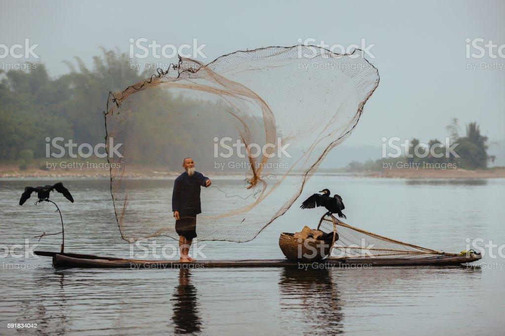 Chinese traditional senior fisherman throwing fishing net Li River China stock photo