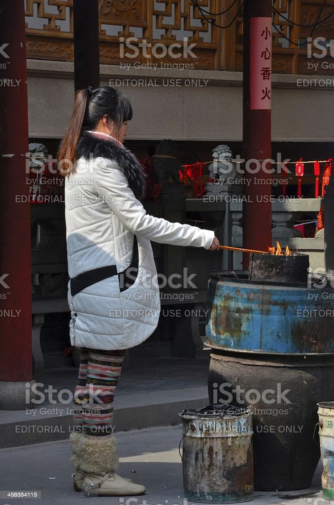 Chinese woman burns incense offering at Taoist temple royalty-free stock photo