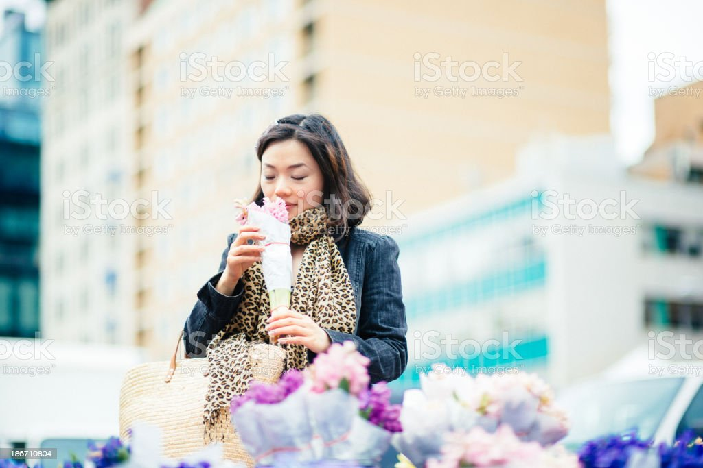 Chinese Woman buys flowers from Street Market Stall royalty-free stock photo