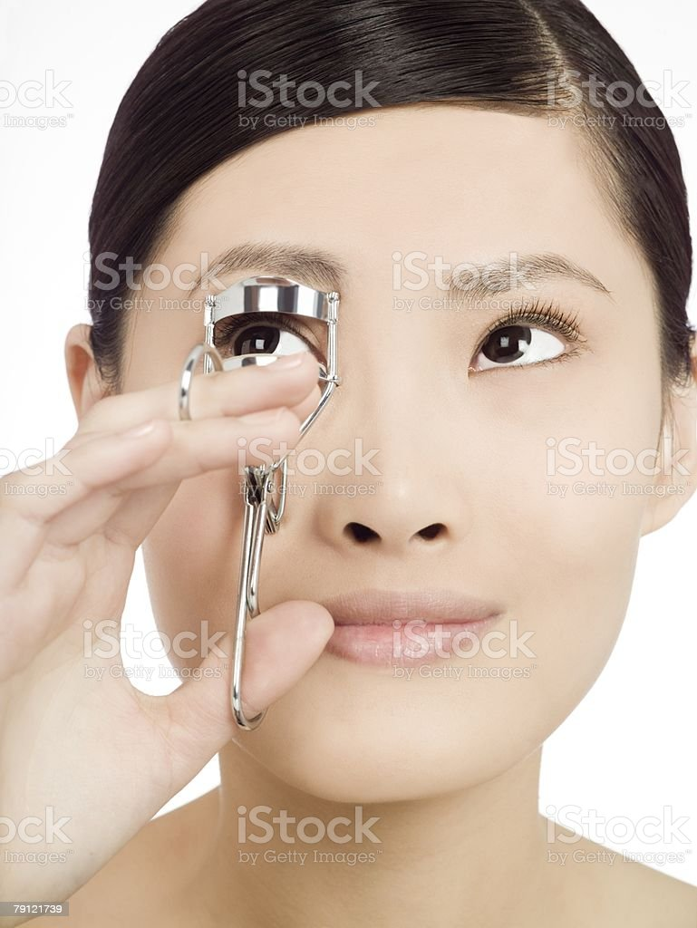 Chinese woman curling eyelashes royalty-free stock photo