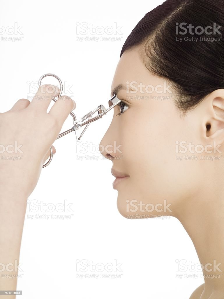 Chinese woman curling her eyelashes stock photo
