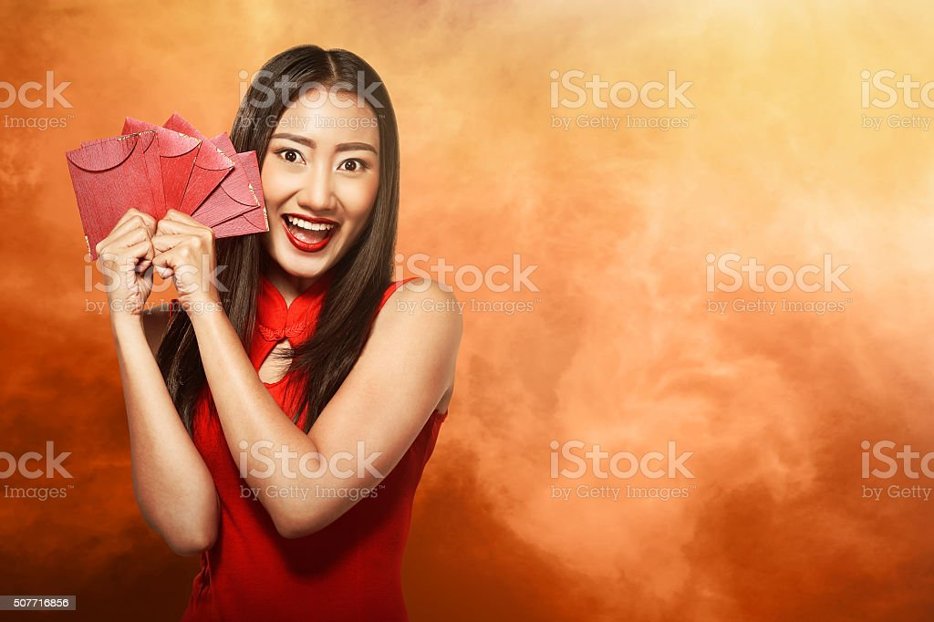Chinese woman in tradional clothing holding angpao stock photo