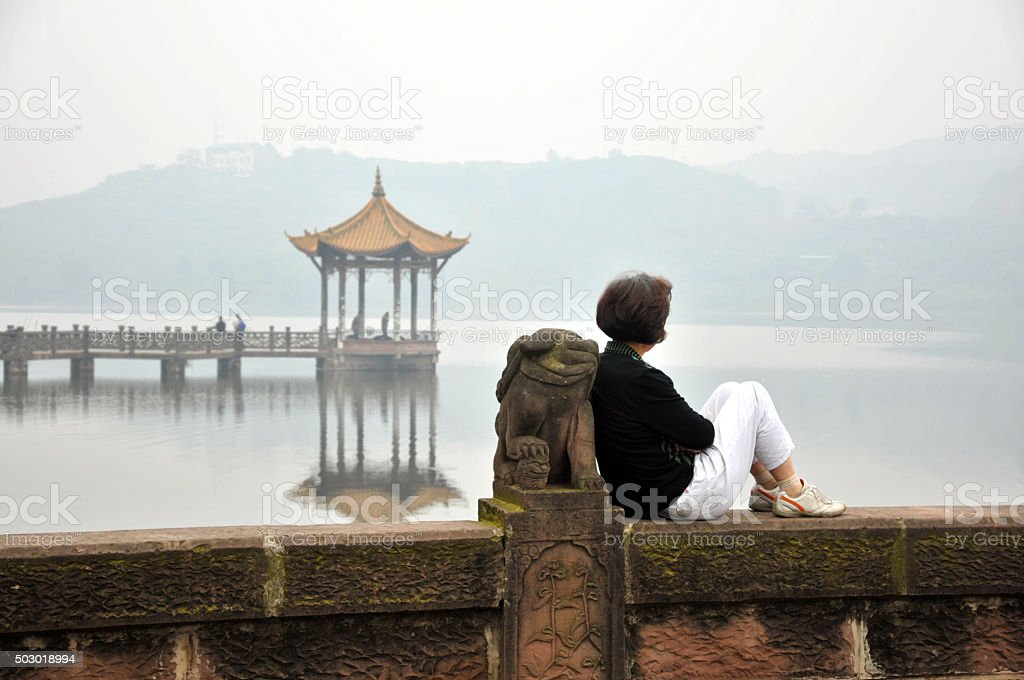 Chinese woman relaxes on lake stock photo