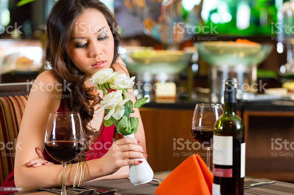 Chinese woman waiting in restaurant for date stock photo