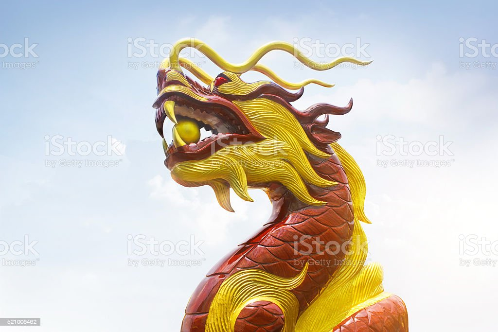 Chinese wooden carve dragon, red and golden colors on sky stock photo