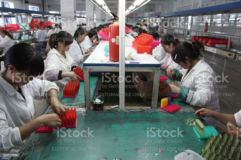 Chinese workers assembling lighters in factory. stock photo