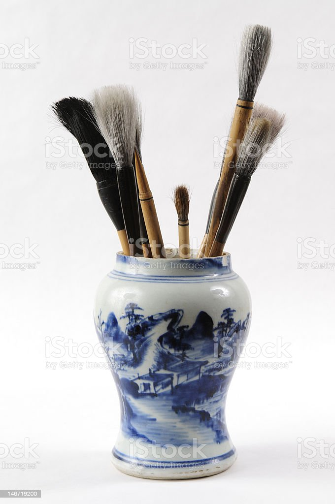 Chinese writing brushes in antique Ming dynasty porcelain jar royalty-free stock photo