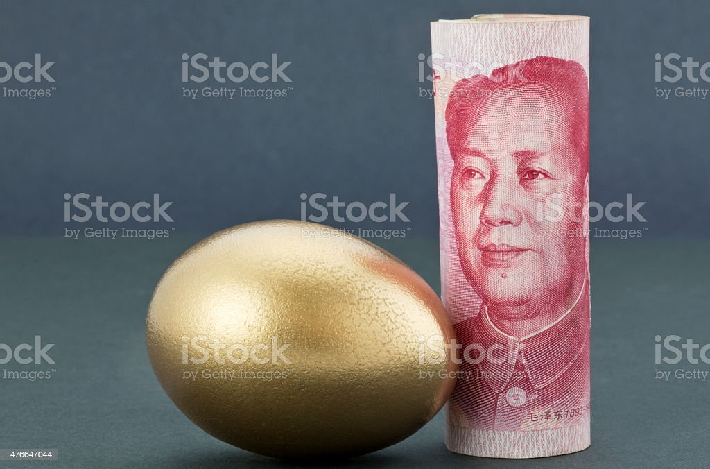 Chinese yuan money with gold egg on tranquil dark background stock photo