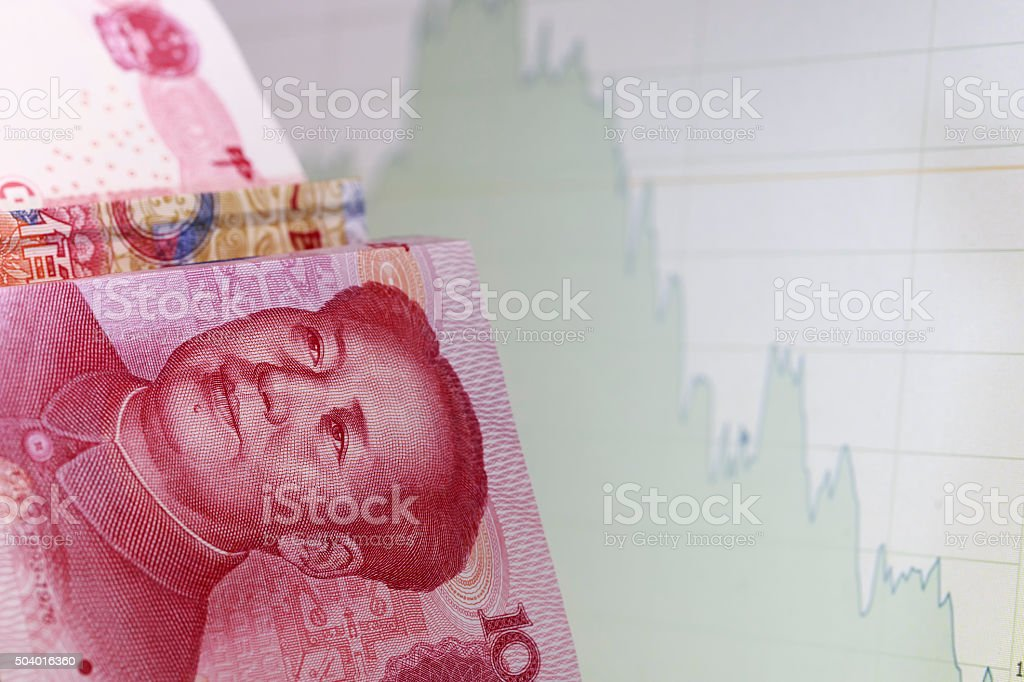 Chinese Yuan Note and falling down financial chart stock photo