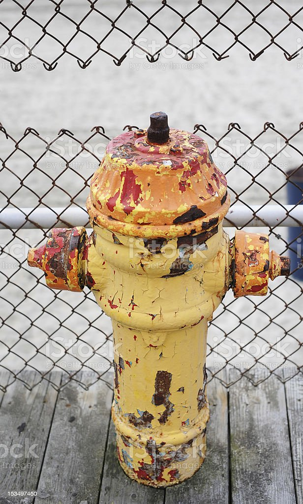 Chipped Hydrant with Fence Cutout stock photo