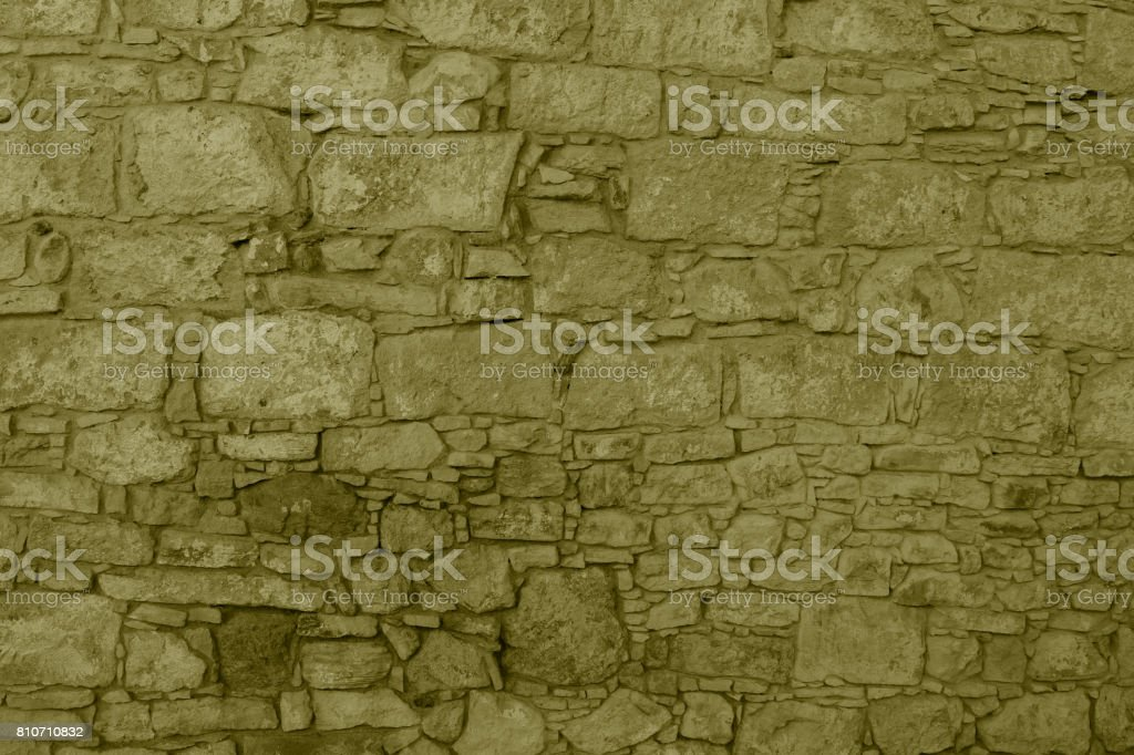 Chipped stone wall texture and background. Khaki color. Ancient building. High resolution stock photo