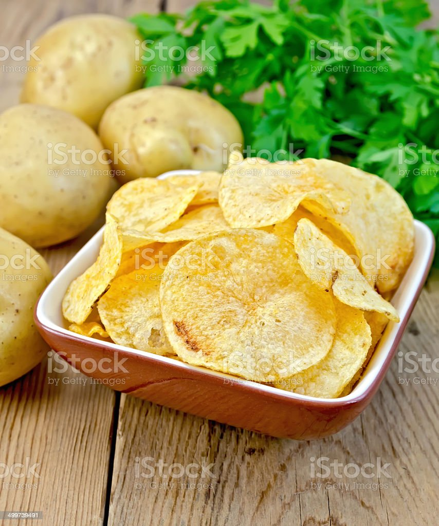 Chips in a bowl with a potato on the board stock photo