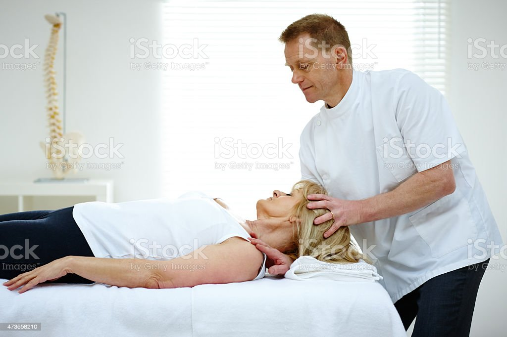 Chiropractor adjusting neck muscles of patient stock photo