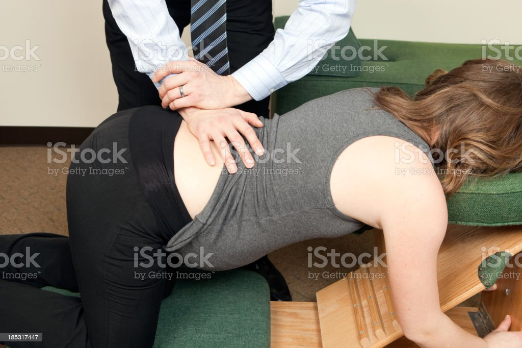 Chiropractor Adjusting Pregnant Woman's Back stock photo