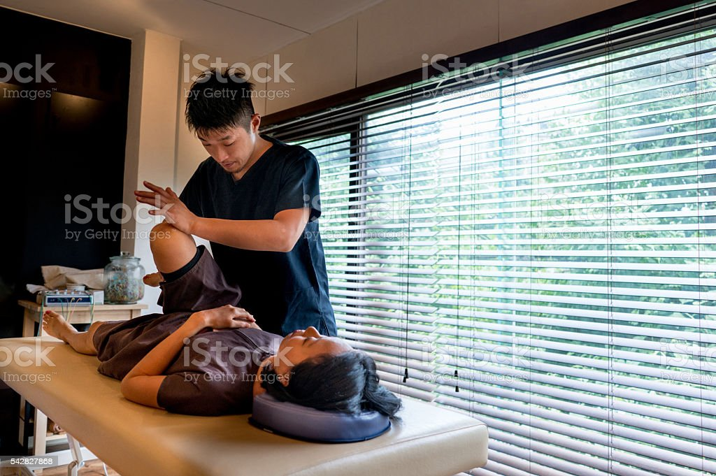 Chiropractor aligning a woman at his practice stock photo