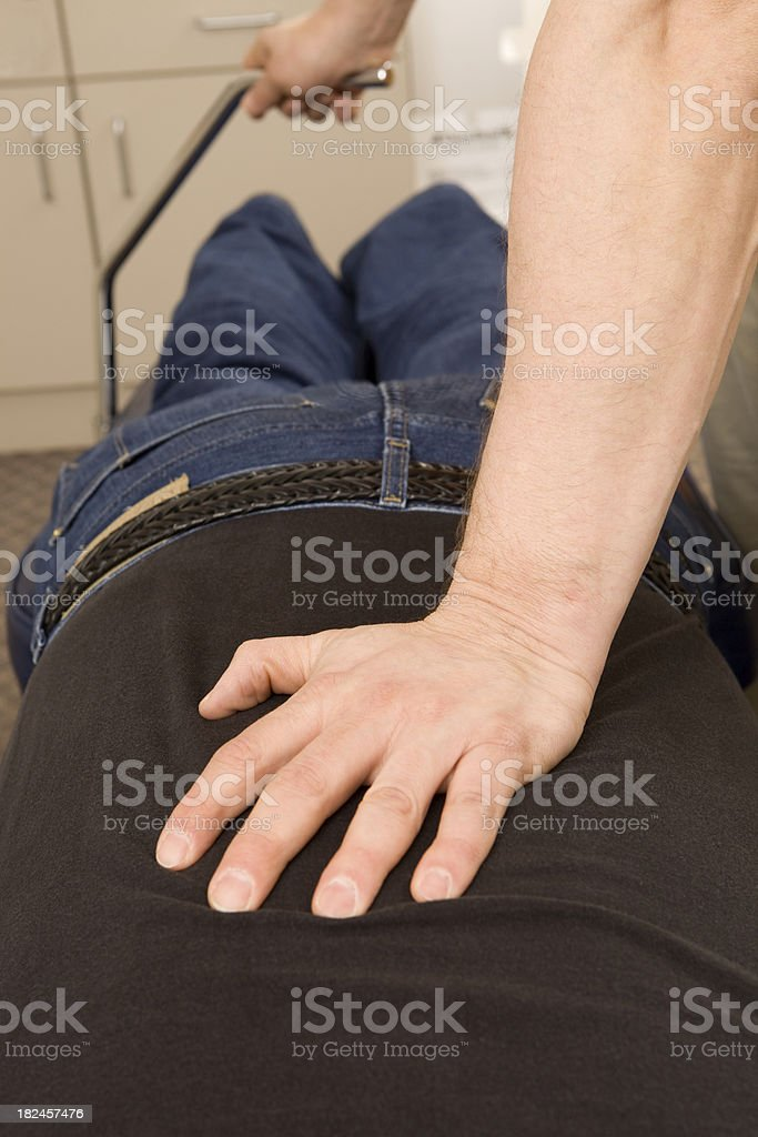 Chiropractor Applying Flexion Distraction Technique to Patient's Lower Back stock photo