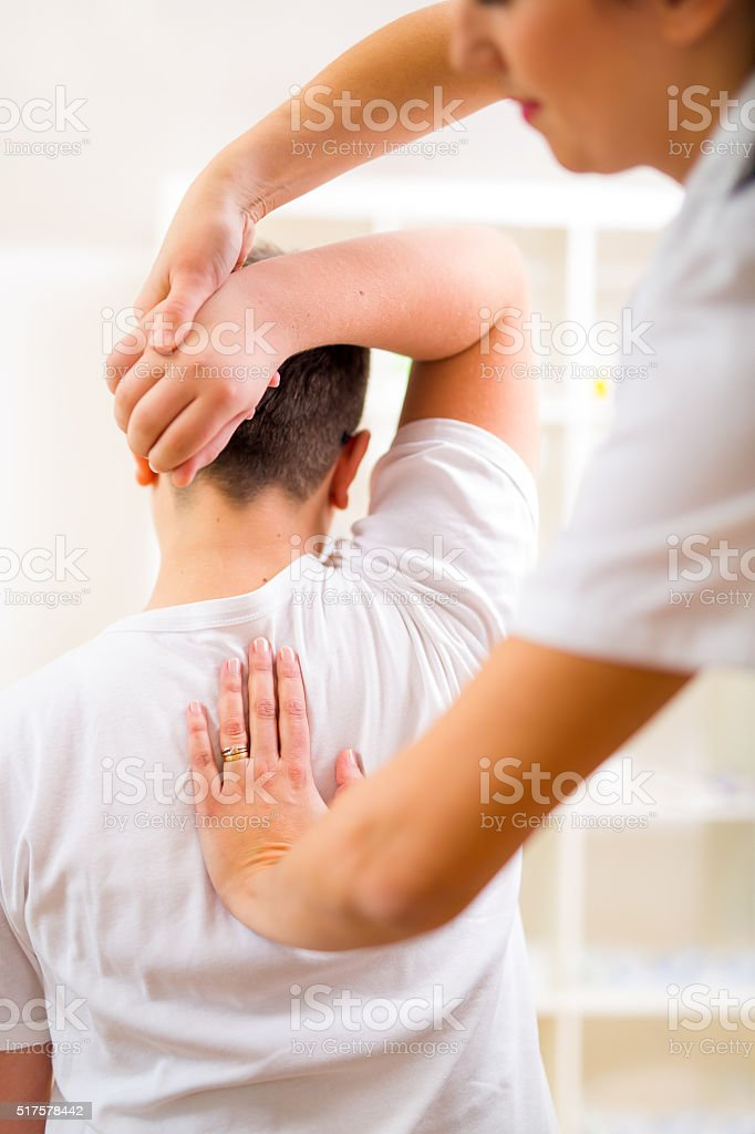 Chiropractor doing adjustment on male patient. Selective focus stock photo