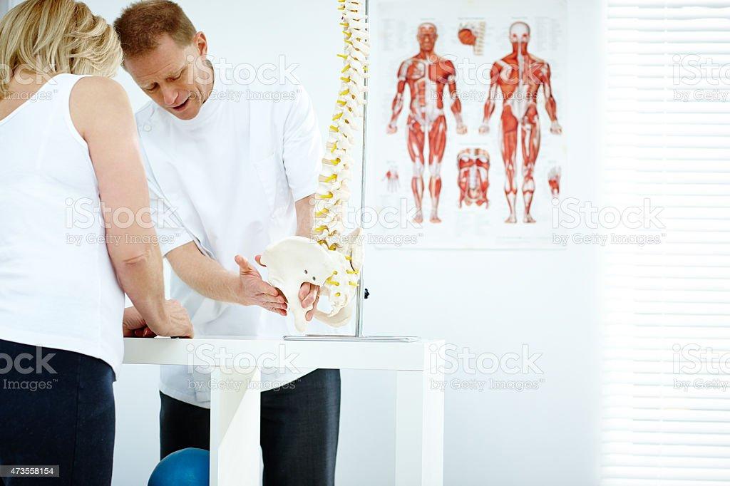Chiropractor explains patient using plastic model stock photo
