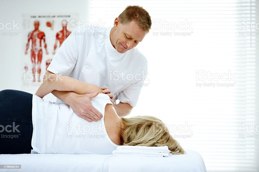 Chiropractor massaging back of female patient stock photo