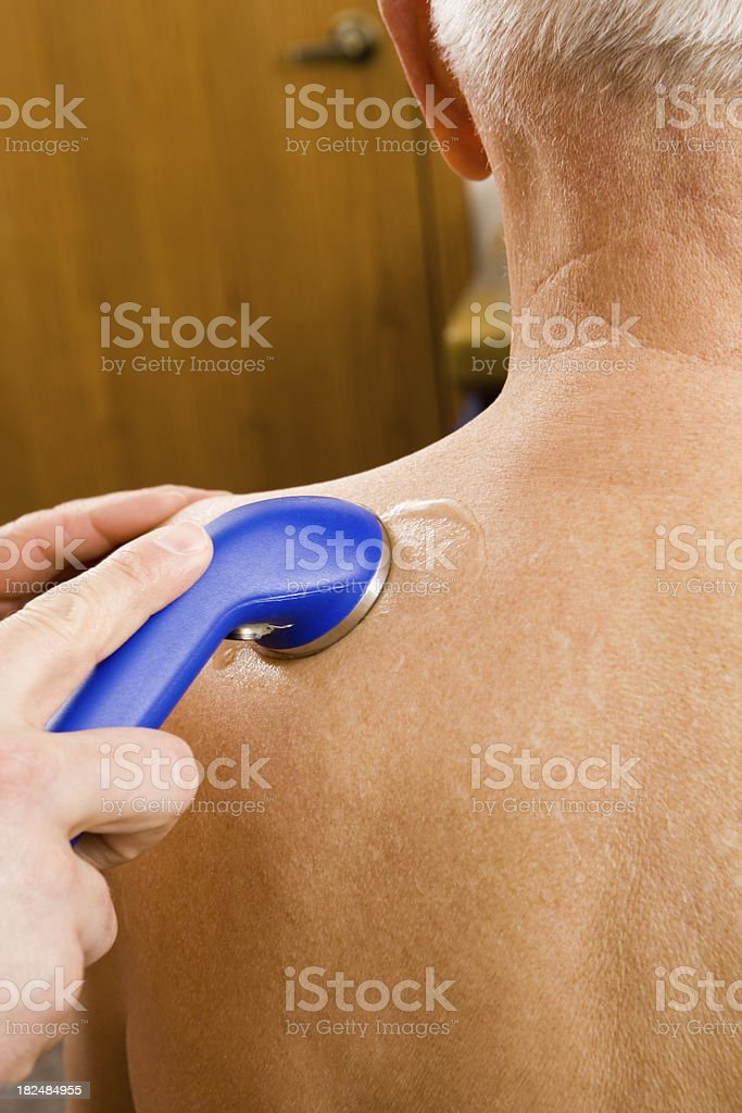 Chiropractor Performing an Ultrasound on a Senior Patient's Shoulder royalty-free stock photo
