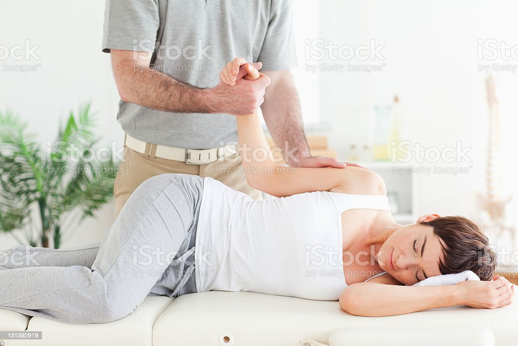 Chiropractor stretches female customer's arm royalty-free stock photo