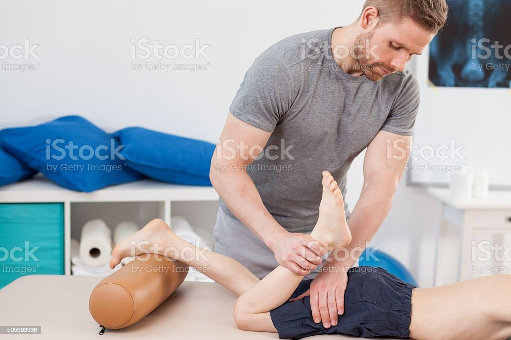Chiropractor stretching boy's leg stock photo