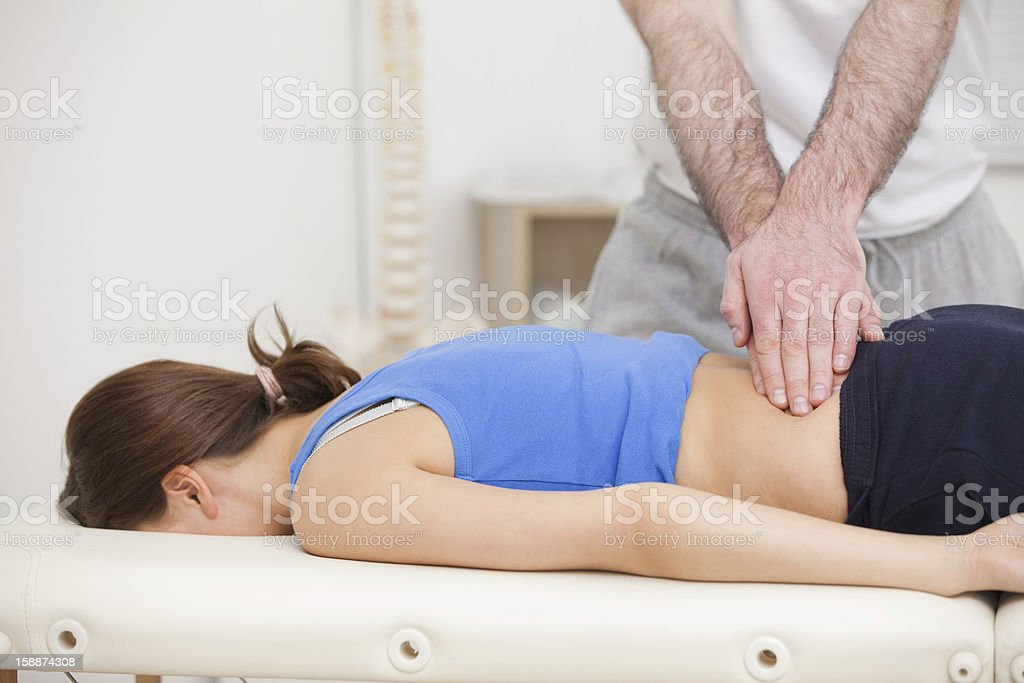 Chiropractor touching the back of woman while standing stock photo