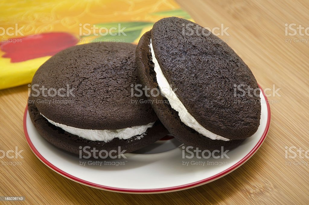 Chocolate and cream giant whoopie pies on a plate stock photo