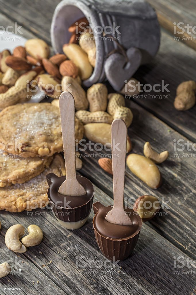 chocolate and nuts on wooden background stock photo