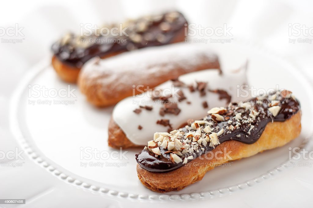 Chocolate and vanilla eclairs on the ceramic plate stock photo