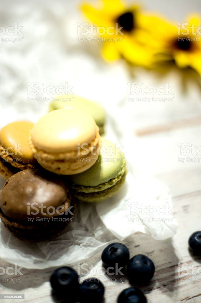Chocolate and vanilla macaroons and blueberry on the wooden table stock photo