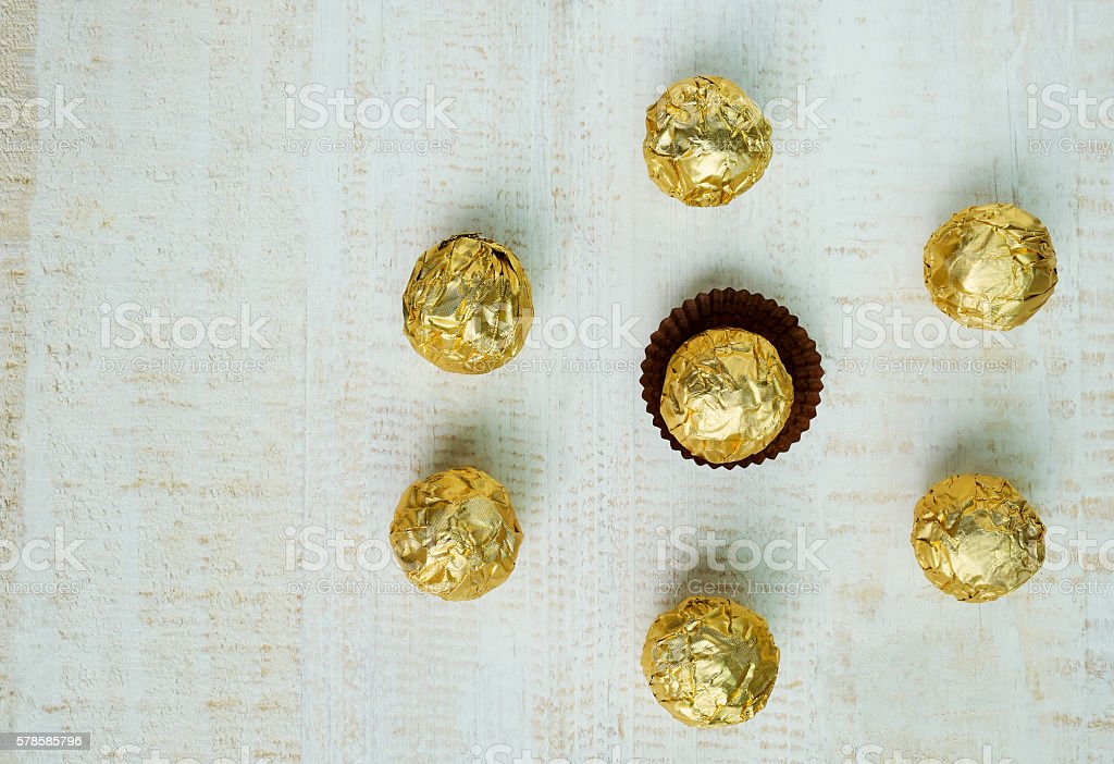 Chocolate ball wrapped in foil, chocolate background Lizenzfreies stock-foto
