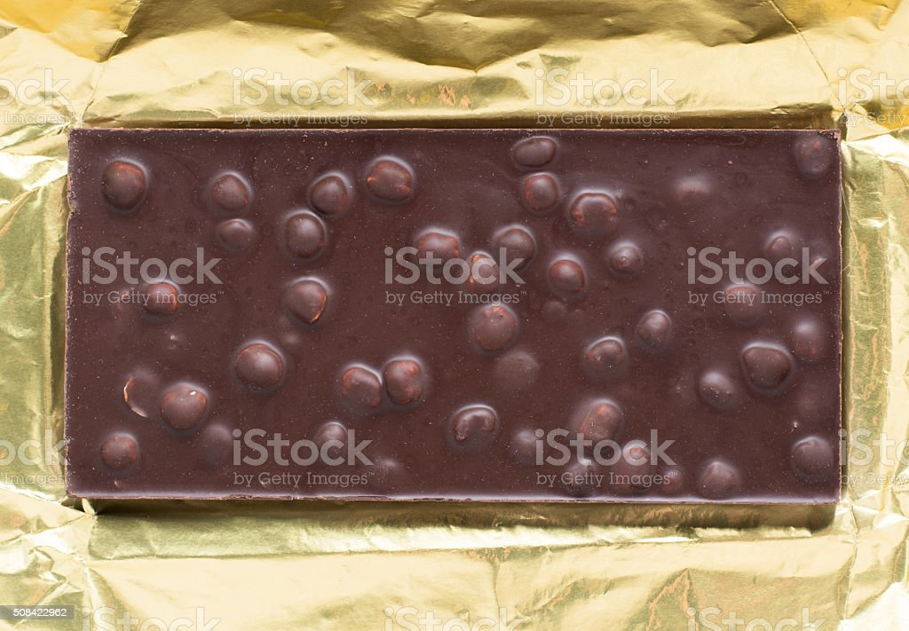 Chocolate bar with nuts in open gold foil wrapping stock photo