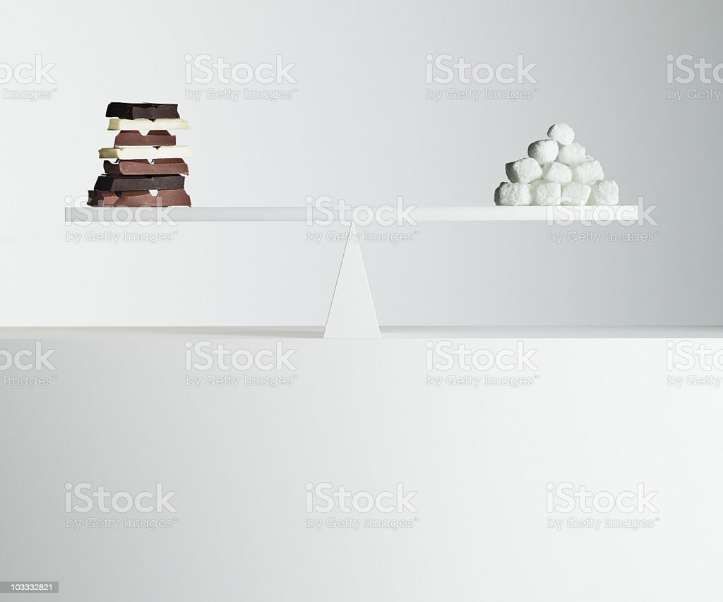 Chocolate bars and stack of sugar cubes balanced on seesaw royalty-free stock photo