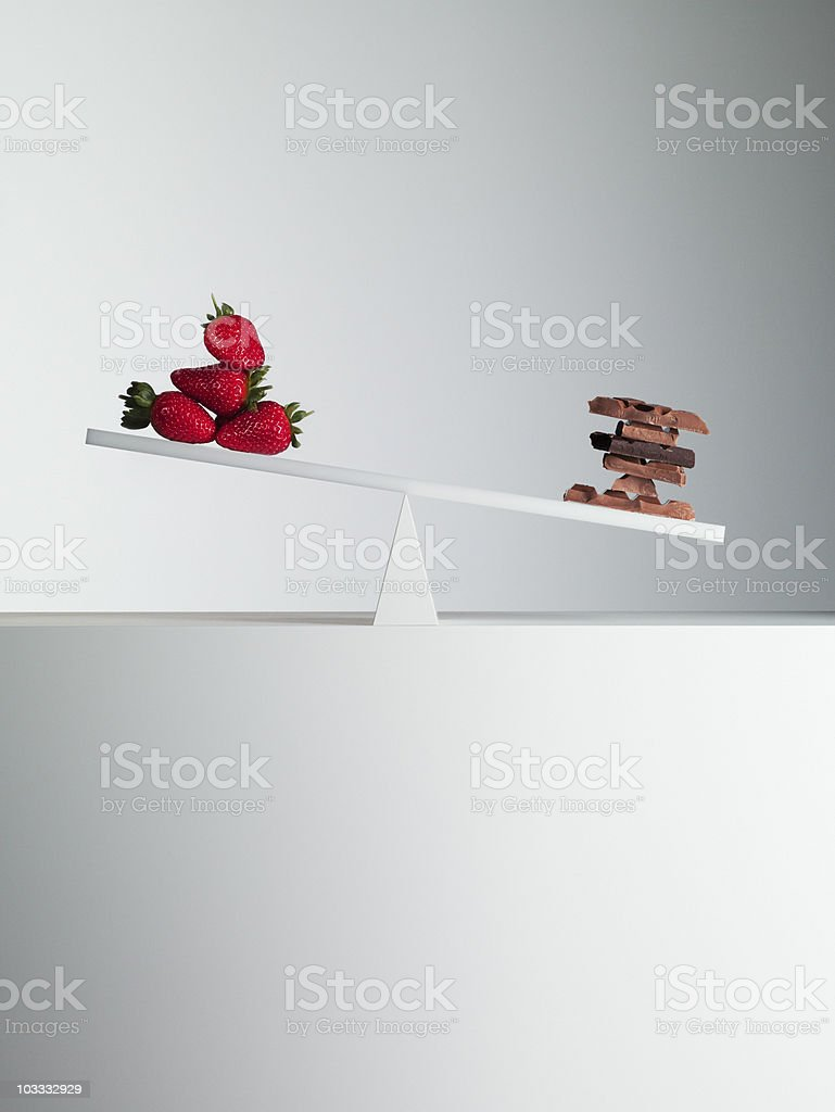 Chocolate bars tipping seesaw with strawberries on opposite end stock photo