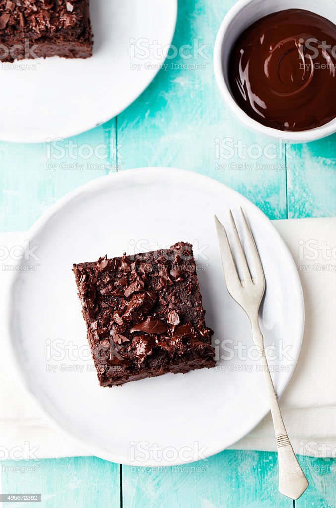 Chocolate brownie, cake, white plate on a turquoise wooden background stock photo