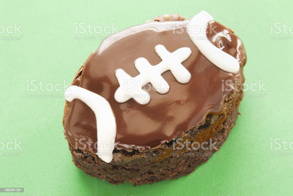 chocolate brownie shaped and decorated like a football green background stock photo
